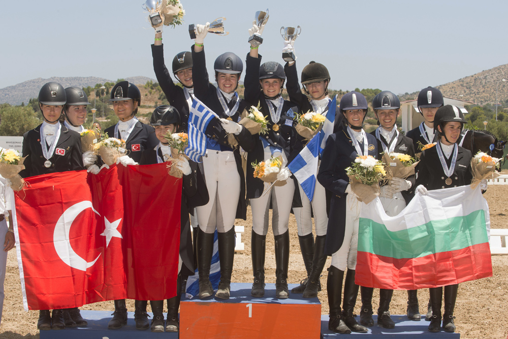 A happy moment on the podium during the presentation of the Junior Team medals at the FEI Balkan Dressage Championshps 2016 in Athens (GRE) last weekend. (L to R): Bulgaria's bronze medallists Stephanie Neseva, Irina Nikolva, Mirela Raikova and Katerina Tvetanova; the newly-crowned Greek champions Elisavet Maika, Lavinia Macropoulou, Eleni Retsou and Theodora Livanos: and Turkey's silver medallists Dila Akbackaloglu, Iren Kaplan, Derin Lara Ekici and Lara Tumay. © FEI/Alexis Valilopoulos