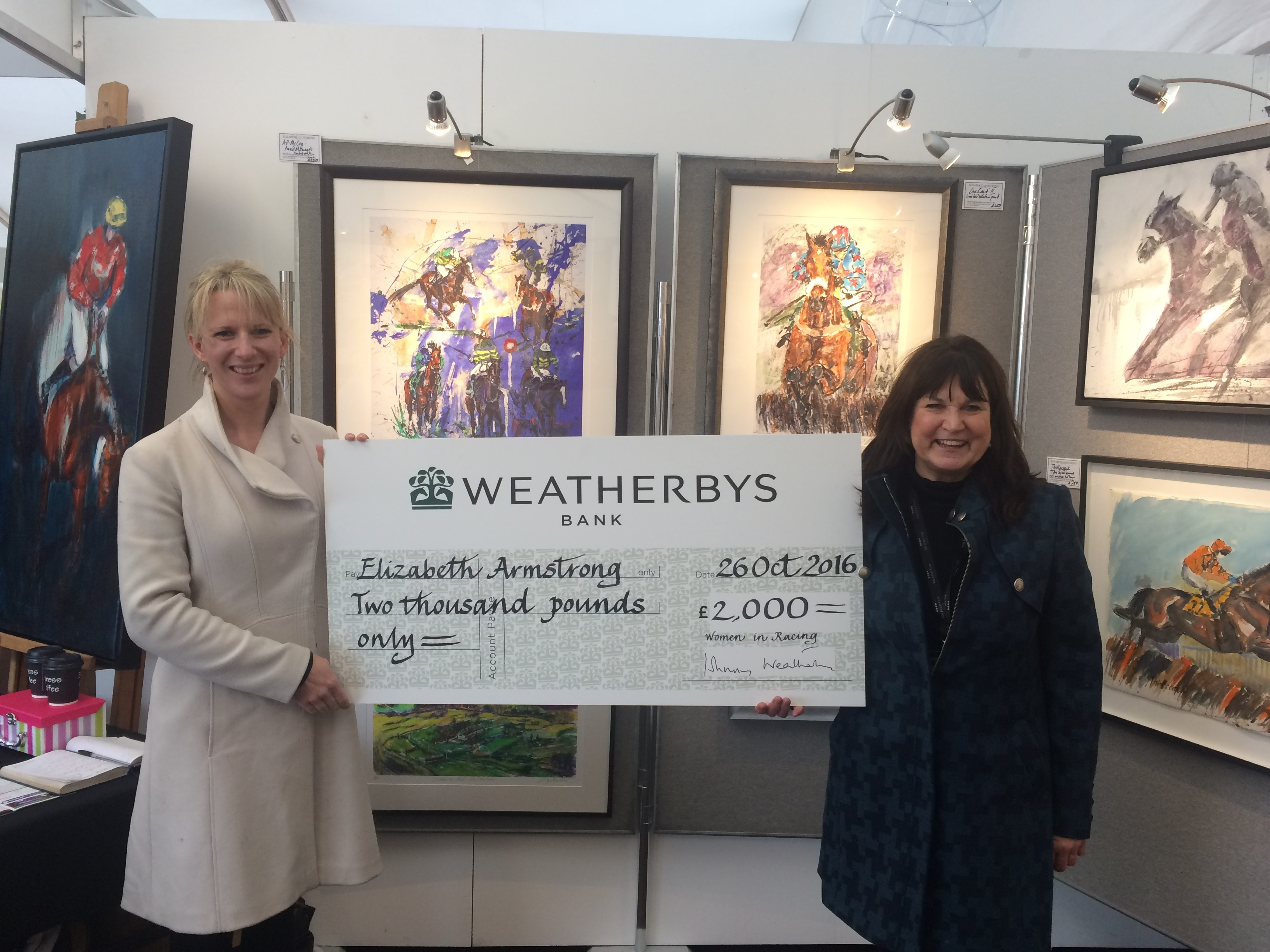 WiR committee member Naomi Mellor (left) presents Elizabeth Armstrong with a £2000 bursary award at Cheltenham Racecourse.